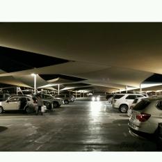 A fleet of cars under a desert tent garage.